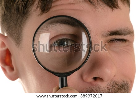 portrait of young man looking through a magnifying glass closeup
