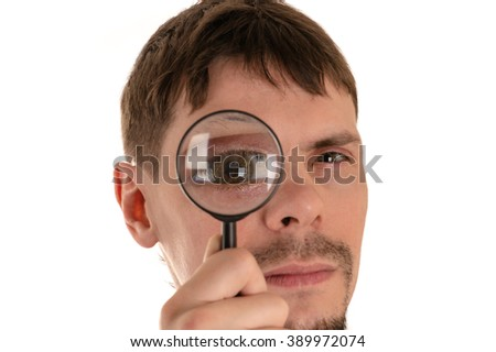 portrait of young man looking through a magnifying glass giant eye
