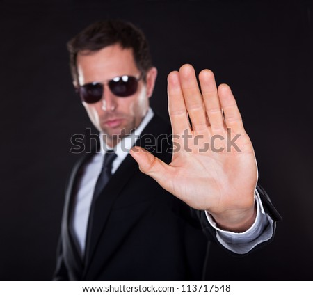 Portrait Of Young Man Making Stop Gesture Isolated On Black Background - stock photo