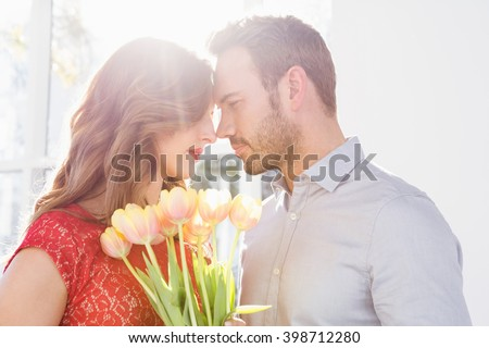 Portrait of young man offering flower bouquet to beautiful woman - stock photo