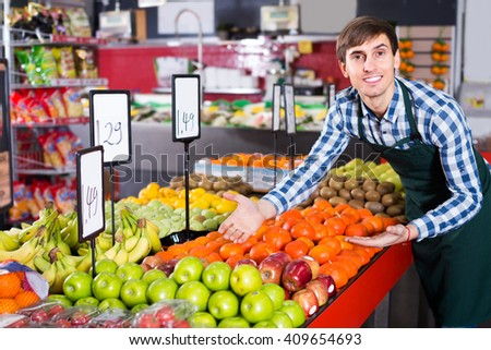 Portrait of young man offering fruits in hypermarket and smiling