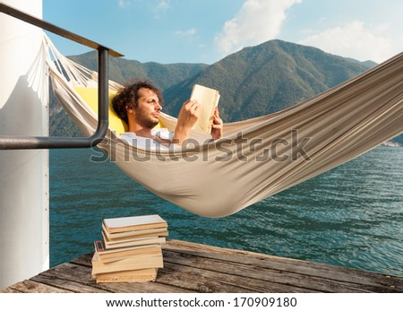 portrait of young man on the dock of Lake  - stock photo