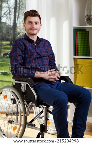 Portrait of young man on wheelchair at home - stock photo