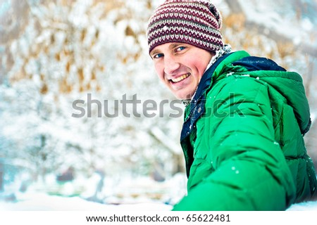 Portrait of young man outdoor resting on bench in winter park - stock photo