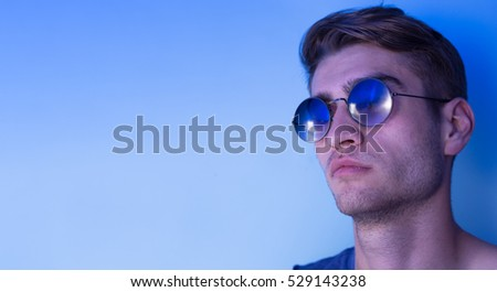 portrait of young man over blue background wearing sunglasses.