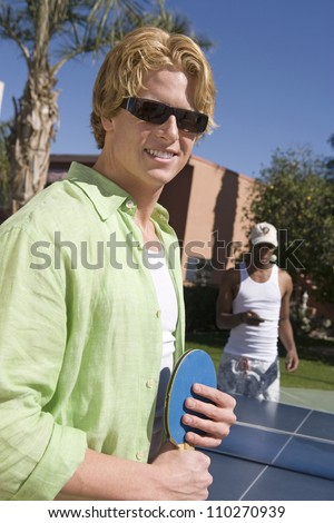 Portrait of young man playing table tennis