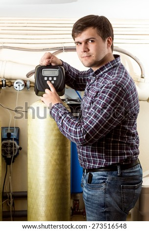 Portrait of young man pressing button on industrial equipment control panel - stock photo