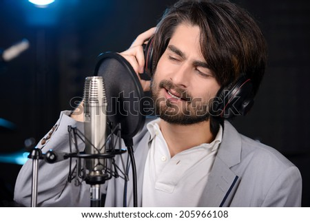 Portrait of young man recording a song in a professional studio - stock photo
