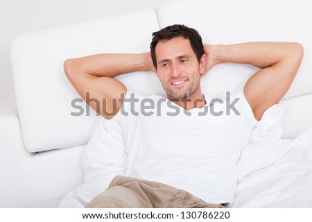 Portrait Of Young Man Relaxing On Bed, Indoors