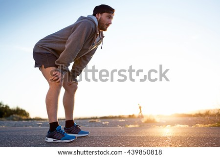 Portrait of young man resting after running in the street. - stock photo