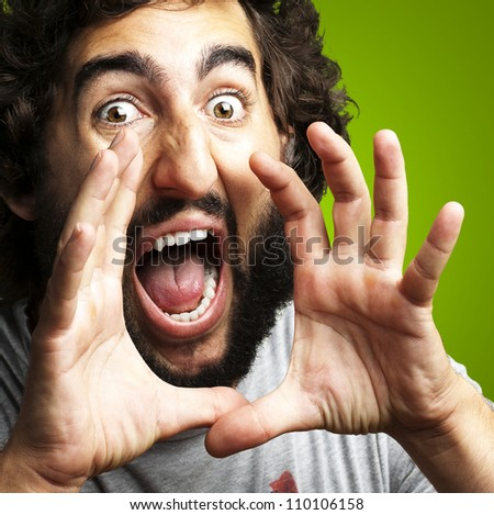 portrait of young man screaming against a green background - stock photo