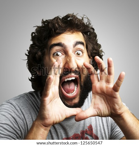 portrait of young man screaming against a grey background
