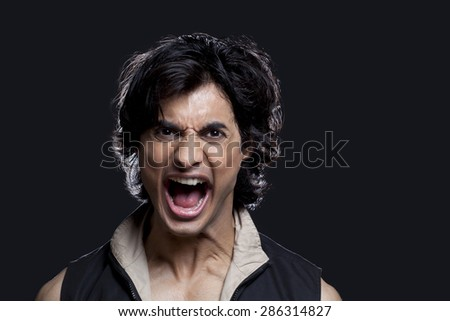 Portrait of young man screaming against black background