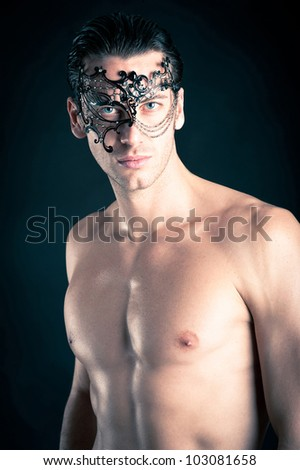Portrait of young man shirtless against black background. - stock photo