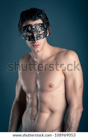 Portrait of young man shirtless with carnival mask against dark background.