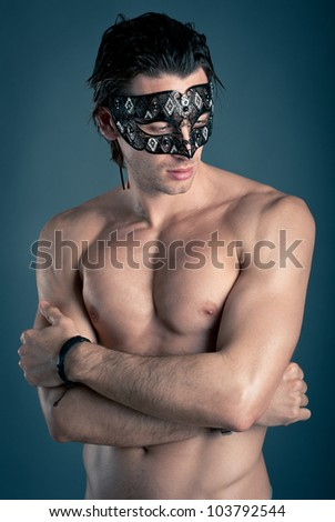 Portrait of young man shirtless with mask against dark background. - stock photo