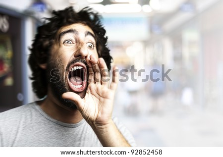 portrait of young man shouting against a crowded place