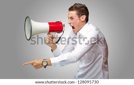 Portrait Of Young Man Shouting And Holding Megaphone Isolated On Grey Background