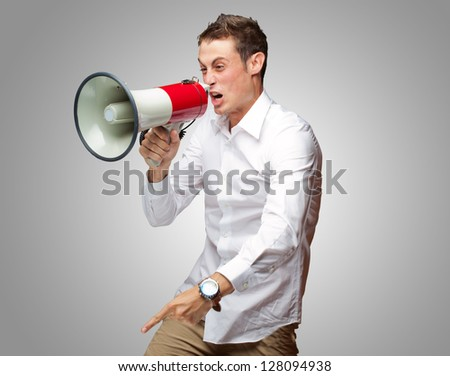 Portrait Of Young Man Shouting On Megaphone Isolated On Grey Background