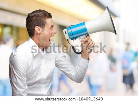 Portrait Of Young Man Shouting On Megaphone Outdoor