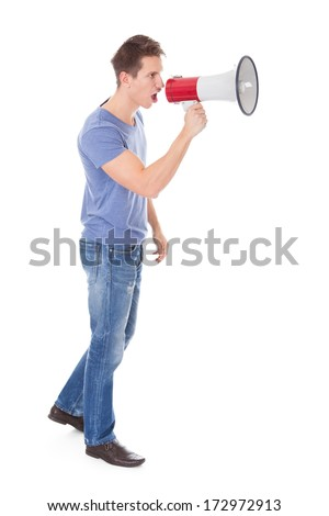 Portrait Of Young Man Shouting Through Megaphone Over White Background