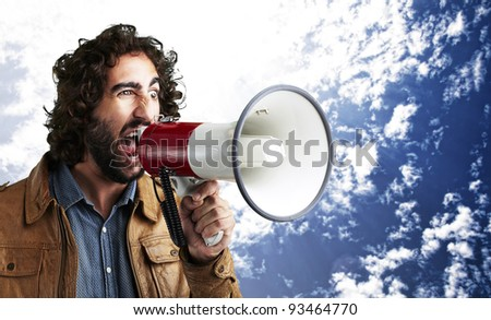 portrait of young man shouting with megaphone against a cloudy sky background - stock photo