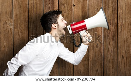 portrait of young man shouting with megaphone against a wooden wall - stock photo