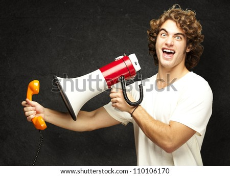 portrait of young man shouting with megaphone and talking on vintage telephone against a grunge wall - stock photo