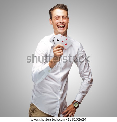 Portrait Of Young Man Showing Poker Cards On Gray Background - stock photo