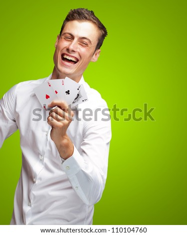 Portrait Of Young Man Showing Poker Cards On Green Background - stock photo
