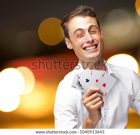 Portrait Of Young Man Showing Poker Cards, Outdoor