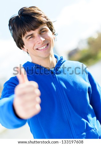 Portrait Of Young Man Showing Thumb-up Sign; Outdoors - stock photo