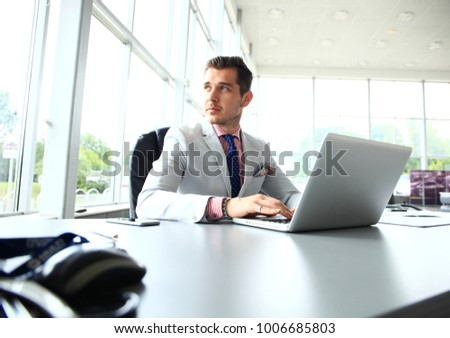 Portrait of young man sitting at his desk in the office. Young employee looking at computer monitor during working day in office