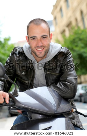 Portrait of young man sitting on motorcycle in town - stock photo