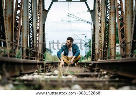 Portrait of young man sitting on the railroad bridge. Vintage Instagram style effect, soft and selective focus, strong clarity, grain texture visible on maximum size - stock photo