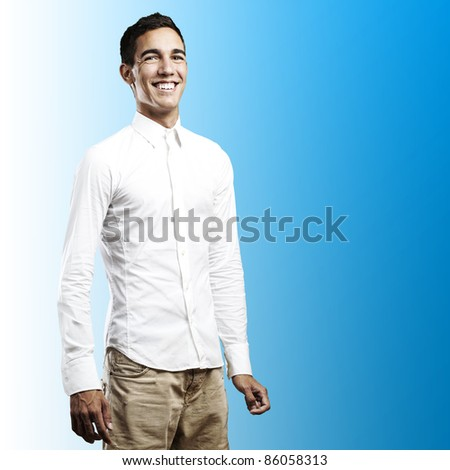 portrait of young man smiling against a blue background