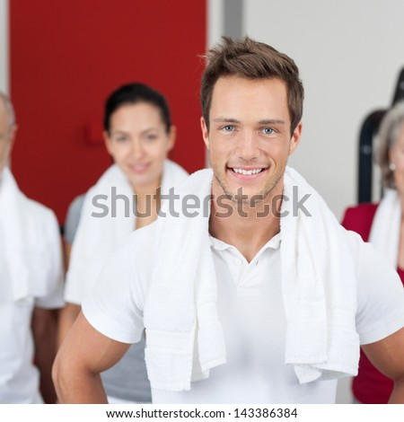 Portrait of young man smiling with group in gym - stock photo