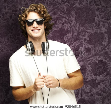 portrait of young man smiling with headphones against a vintage wall