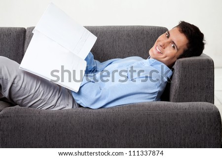 Portrait of young man smiling with magazine while lying on sofa - stock photo