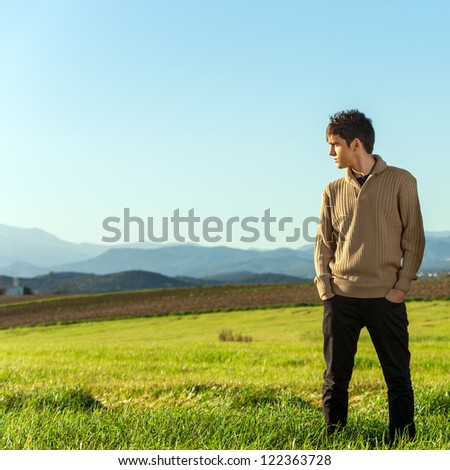 Portrait of young man standing in green field. - stock photo