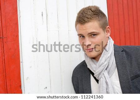 Portrait of young man standing on garage door - stock photo