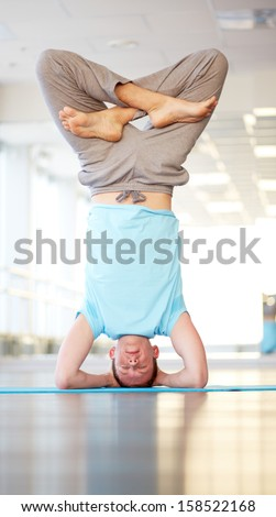 Portrait of young man standing upside down with his legs crossed - stock photo