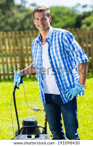 portrait of young man standing with lawnmower at home garden - stock photo