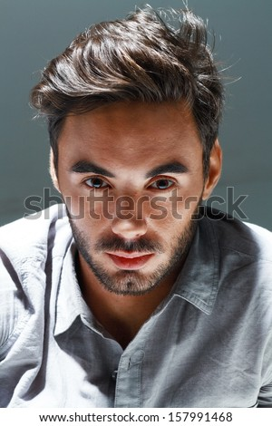 Portrait of young man studio shot with very handsome face in grey casual shirt against dark background  - stock photo