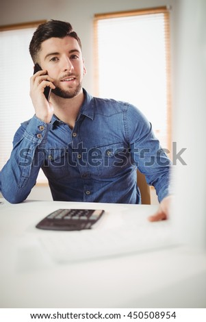 Portrait of young man talking on phone at office