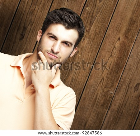 portrait of young man thinking against a wooden wall - stock photo