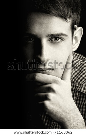 Portrait of young man thinking 3, black background - stock photo