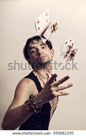 Portrait of young man throws playing cards