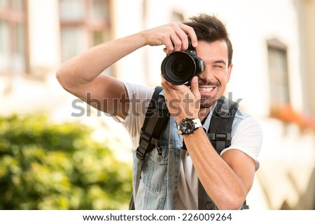 Portrait of young man, tourist. He is holding digital camera. - stock photo