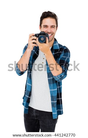 Portrait of young man using camera on white background - stock photo